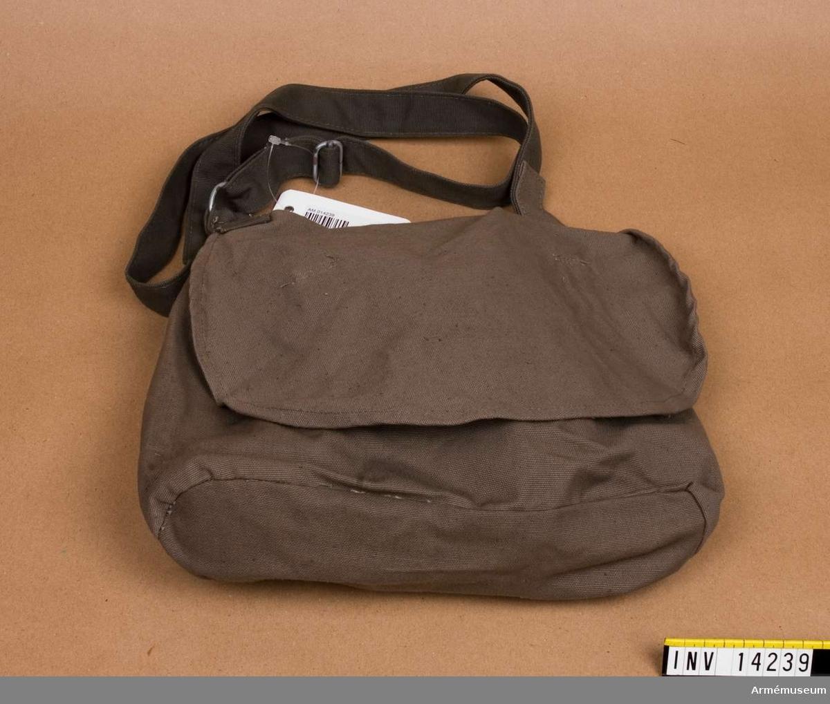 """Grupp C I Brödväskan består av svart färgat linne (32 cm lång och 26 cm bred) med lock, som stänges med två svarta knappar, fastsydda vid väskan. Väskan har på lockets baksida stämplar: """"1882"""", """"PRM"""" - provmassigt modellenligt.  Väskan har innerpåse av grovt linnelärft med fickor och stämpel: """"PRM"""", samma betydelse. Axelgehäng av svart läder, 2,5 cm bred med spännen av vitmetall. """"PRM"""" och """"1878"""""""