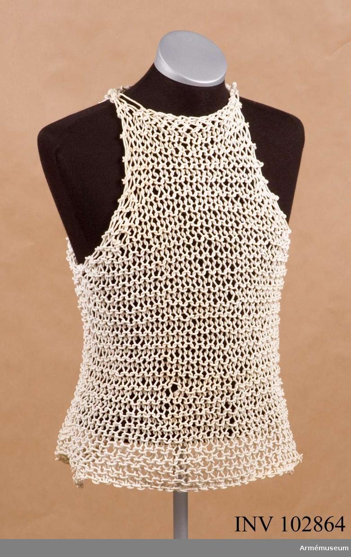 """Skjorta av vita snören, som är bundna genom knutar liksom ett nät. Skjortan är utan ärmar och krage samt har en pappersetikett med påskriften: """"Size 2 1943"""" uppåtriktat pil """"Job. White & Sons. Ltd. 81"""" (firmas stämpel)."""