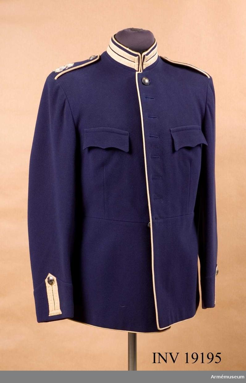 """Av blått kläde med vita """"knapphål"""" och snören. På axelklaffarna GV I Adolfs monogram i silver, h:60mm. Silverknappar, släta med tre kronor. Svart konstsidenfoder med för """"C B V Karlskrona"""" =centrala beklädnadscentralen.Ingår i samling uniformer från K 1, som blev övertaliga då de fick nyuppsydd paraddräkt m/ä omkring 1975."""