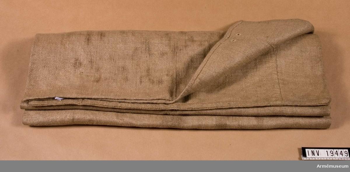 """Säcken har två för hand sydda vändsömmar. Sömmarna finns framtill. Säcken är fållad längst upp och märkt """"SHG 865. 9. 5 FDM""""."""