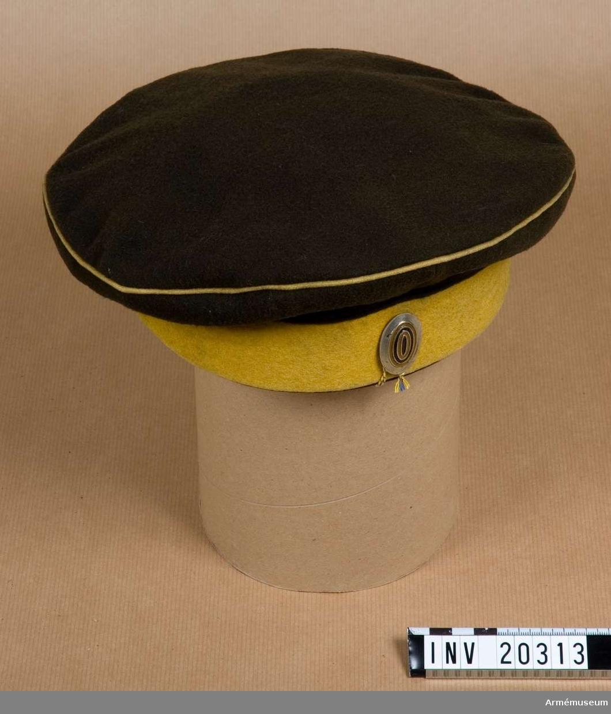 """Grupp C I. För menig vid 7. Kinburna dragonregementet, tidigare 19:e Kinburna dragonreg:t, storfurst Mikael Nikolaevitsch regemente, 1. reg:t 7. kavalleridivision. Mössa, tallriksmodell, av kläde. Består av två delar; övre delen av svart kläde med gul passpoal på övre kanten: nedre delen av gult kläde. På framsidan en oval kokard av järn (soldatkard) målad i orange och svart (S:t Görans färger).  Foder av grov linnelärft. LITT Knötel-Sieg, Handbuch der Uniformenkunde, Hamburg 1937, sida 327. Denna mössa infördes i ryska armén (kavalleriet) år 1882 samtidigt med andra förändringar i den ryska unifor- men (""""nationaluniform""""). S. Sawage, Kejserliga ryska armén, S:t. Petersburg 1894, sida IX: Uniform nr 104 - regementsuniform."""