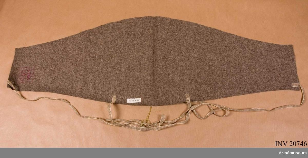 """Grupp C I Av grått kläde i triangelform med två par bomullsband. Gördeln har stämplar: """"OS1 och """"1924""""."""
