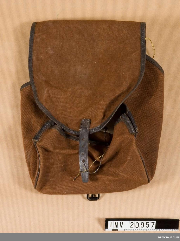 Grupp C II Av brunt tyg i fyrkantig form med lock som har läderrem med spännen att stänga fodralet. Fodralet kantat med läder och har på sidorna två hål för snören att binda fast dem. Fodralet är gjort för att packa in reservportion i mattornister.