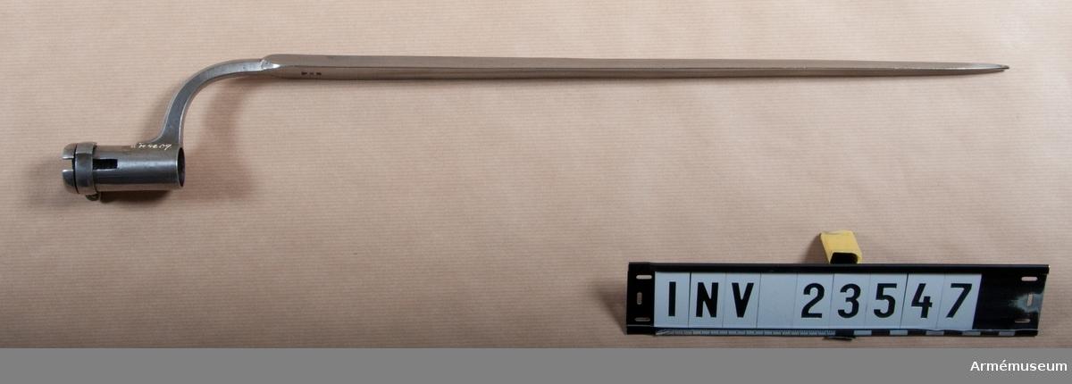 """Grupp E II.  Bajonetten har 64 mm lång hylsa, vars nedre kant är förstärkt. Spåret för bajonettklacken är rakt. Ovanför den förstärkta kanten går en rörlig, 9 mm bred ring kring hylsan. Ringens utåtvikta ändar hophållas av en skruv. Mitt emot ändarnas föreningspunkt är ringens framkant på en sträcka av 22 mm urtagen så att ringens bredd där är 7 mm. I hylsan är en nit isatt vilken ligger an mot framkanten på detta urtagna parti. Niten hindrar dels att ringen går framåt på hylsan, dels att ringen vrides mer än 22 mm åt vardera hållet. När man skall sätta på bajonetten vrider man ringen så att klackledaren kommer mitt över hylsans spår, """"klackgången"""" och sätter på bajonetten. Därefter vrides ringen åt vänster, varigenom bajonetten fastlåses. Den rörliga ringen kallades """"holk"""", men bajonetthylsans nedre förstärkta kant hette """"ring"""".  Bajonettarmen är fyrkantig. Utsidan är kullrig de övriga plana.  Bajonetten har trekantig stukatklinga vars inre yta snarast har blodrand i stället för de båda andra ytornas jämna urkälning. På bajonettarmen är inslaget PR och på bajonettklingans insida P med prick över, SB, alltså IPSB. J Alm 1941."""
