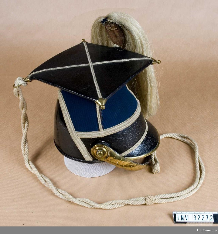 """Grupp C I. Ur uniform för manskap vid Livgardet t häst; 1852-79. Består av vapenrock, epåletter, byxor, lansiärmössa, plym, stövlar, sporrar, halsduk, skärp, kartusch, kartuschhrem,  handskar, sabelkoppel, sabel, balja, sabelhandrem. Mössa enligt go 4/9 1852. Modellapp 4/9 1852. Mössan är speciell - den har på toppen en fyrkantig platta. Hjälmens polska namn är """"tschapka""""."""