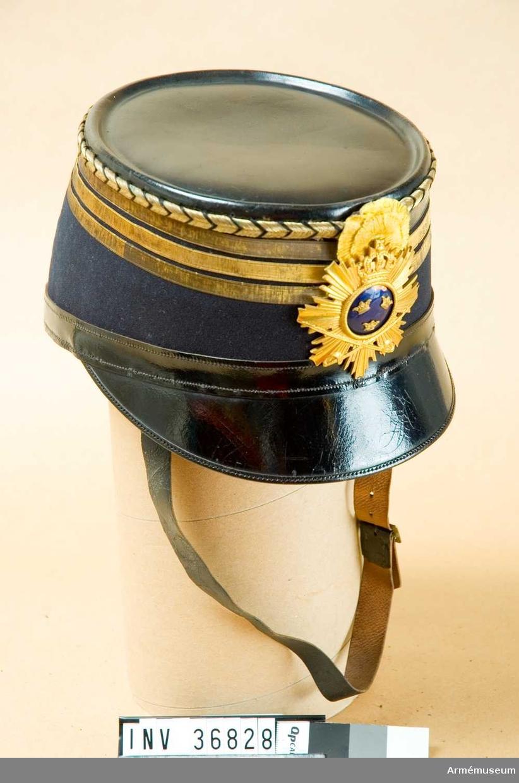 Grupp C I. Ur uniform för parad för officer vid Kungliga Skånska husarregementet. Tillverkad mellan 1895 och 1910. Består av dolma, ridbyxor, kartusch med rem, skärp, handrem, mössa, plym, ridstövlar, sporrar, sabel, balja.Högmössa med plym är inskrivet i accetionskatalog i efterhand.
