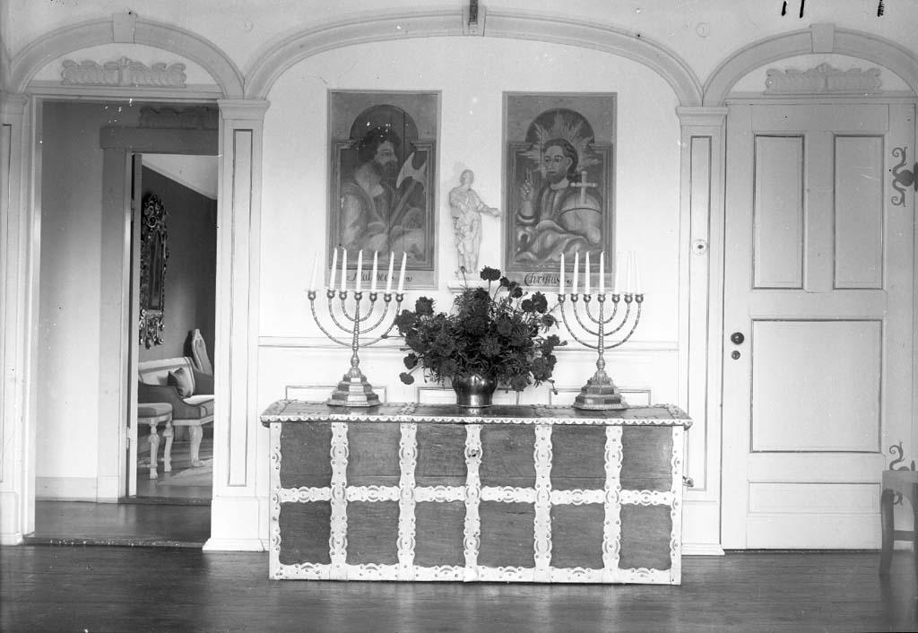"""Enligt fotografen: """"D. 8 sept 1934 (Övre hallen) Konsulinnnan Aspegren Stenungsön"""". Uppgifter från givaren: Övre hallen, kista med två kandelabrar"""
