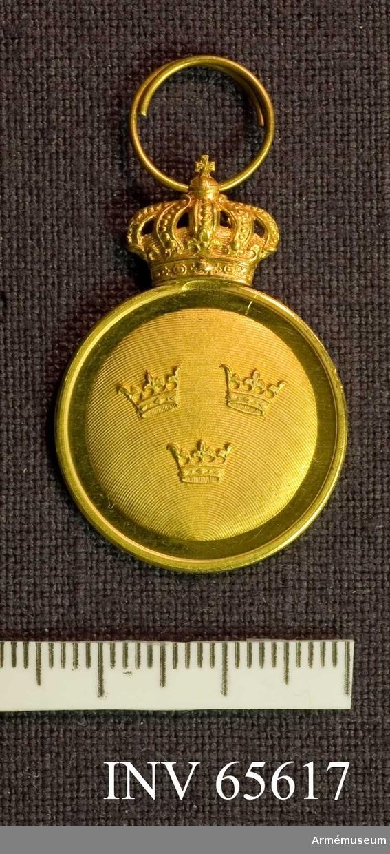"""Grupp M II.     På åtsidan tre öppna kronor, ställda två och en på skrafferad botten.   Frånsidan har ett johanniterkors med en vase i centrum.  Runt vasen """"GUSTAF DEN III INST MDCCLXXII"""".  På medaljen övre kant en kunglig krona."""