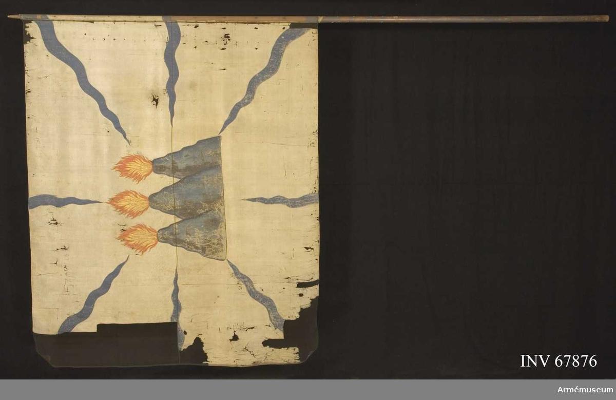 Duk: Tillverkad av enkel taft. Sydd av två våder. Duken fäst med vitt sidenband och förgyllda spikar.  Dekor: Målad (obs! Ej insydd) lika på båda sidor: från hörnen och sidornas mitt blå flammor, i mitten Västmanlands vapen: tre eldsprutande  berg i blågrått med lågor i rött och guld (73 cm h.)
