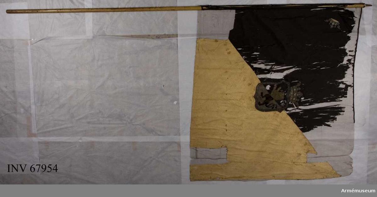Duk: Tillverkad av enkel gul och svart sidenkypert sydd av 3 horisontella våder. Fäst vid stången med en rad tennlickor på svart sidenband.  Dekor: Diagonalt delad i två fält, det övre inre svart, det nedre yttre gult; i mitten broderat omvänt lika på båda sidor med guld och silke Västergötlands vapen. Guldkantad sköld med styckad svart och gyllene duk ett stående lejon i guld på det svarta på guldet i olika ?? och silken, följd av två stjärnor i silver på det svarta fältet en öppen krona i guld och blått silke. Applicerade och broderade i schattersöm i silver. Duken kantad med svart band i överkanten och gult band vid det gula fältet.   Stång av gulmålad furu. Saknar spets och holk.    Katalogisering:Gudrun Ekstrand/Rebecka Enhörning 1976-10-12, inmatning-utskrift PAr 1996-11-14.