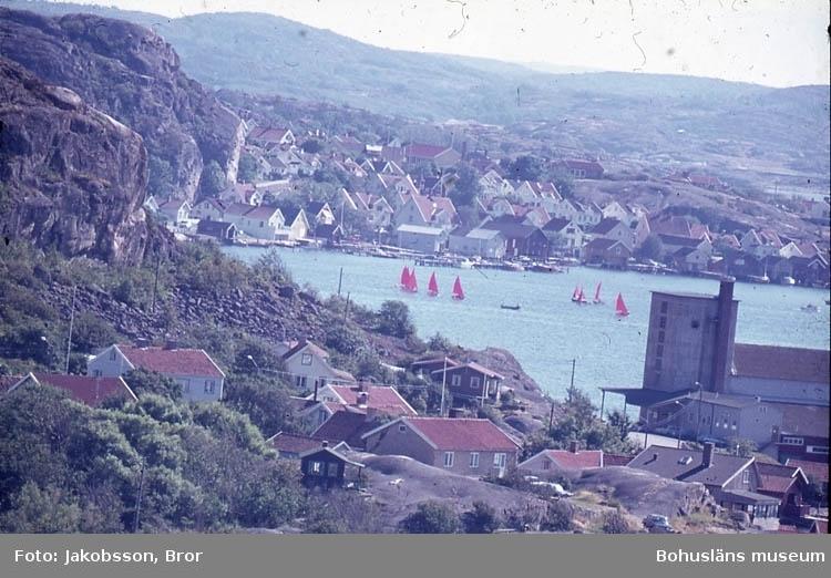 """Enlig Bror J. egen not. """"Från kappseglingar 7 augusti 1976. Mirror med röda segel och Triss, också småbåtar, startade i hamnen och gick runt flagget Valö och Köttö tre gånger. Återfärden mot hamn satte Mirror upp spinnaker. Kölbåtarna gick också ut från hamnen men gick norrut, förbi Valö och tävlade på leden i höjd med Danneholmen, innan de återvände till målet vid Badhusholmen. De kom i mål senare än småbåtarna. Andungarna tävlade även till havs. Jag hade satt mig på Rösekullen och hade utsikt mot båda tävlingsplatserna, men ut till havs nådde inte teleobjektivet och solglittret var ej fotovänligt"""". """"Kapseglingar 7/8 1976 mot Valö och Köttö, samt för Kölbåtarna, norrut förbi Valön mot Danneholmen och tillbaks mot Badhusholmen. Tagna från Rösekullen""""."""