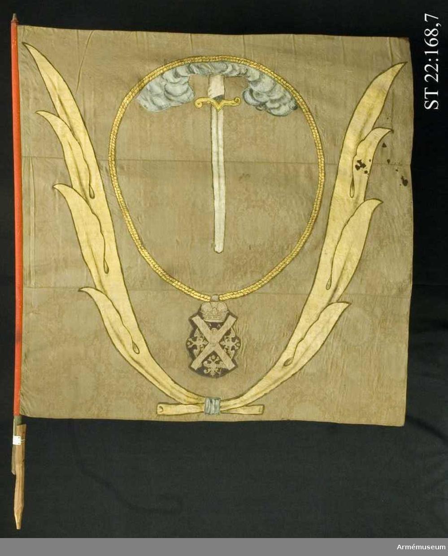 Duk av brun kinesisk sidendamast. Dekor i intarsia och målade detaljer. Motivet föreställer en hand med svärd som kommer ner ur ett moln omgivet av andreasordens kedja med dess insignier nedtill. Det hela omgivet av nedtill korslagda palmkvistar. Stången är skarvad med en grovt tillskuren träbit. Troligen gjort i utställningssyfte under 1800-talet.
