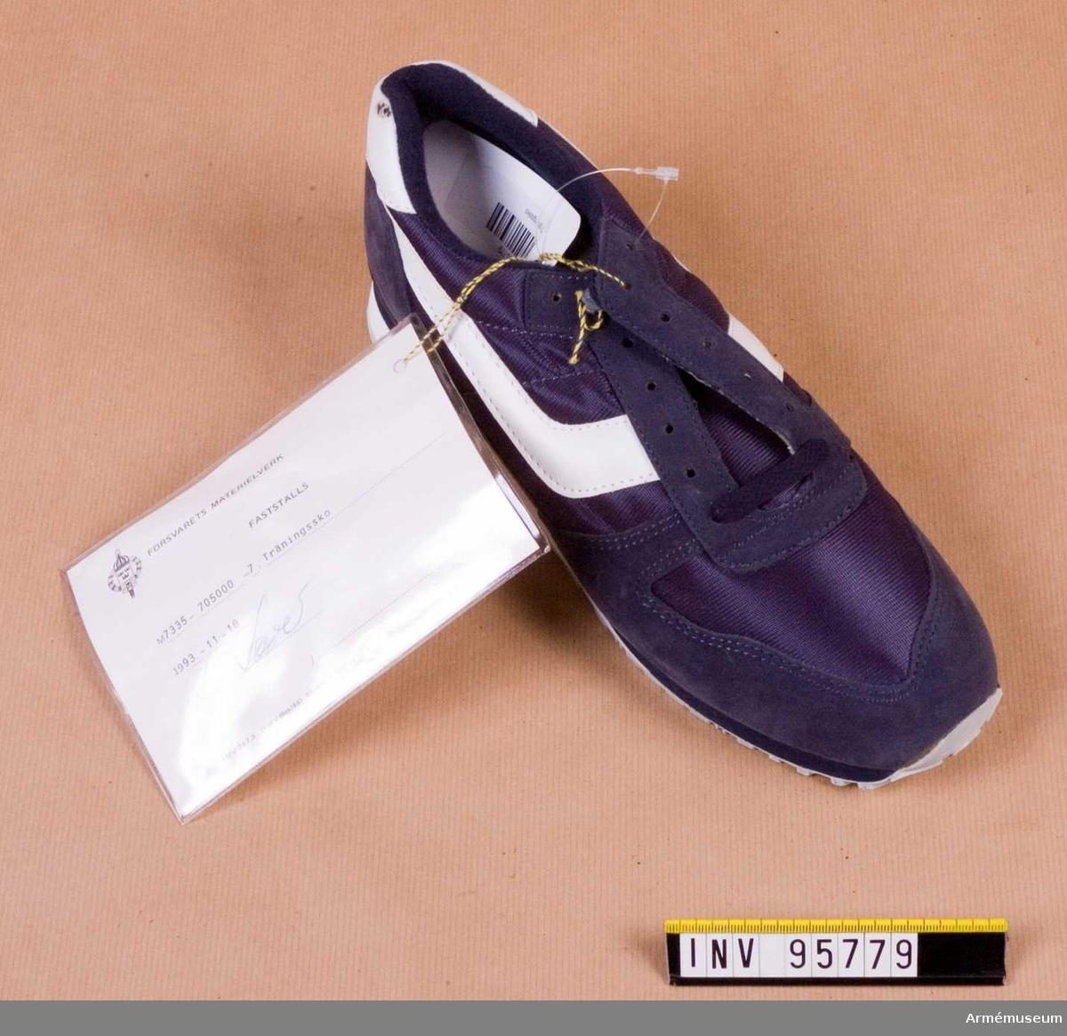 """Höger sko. Skorna är gjorda av syntetväv, mockaspaltskinn och gummi och har lös inläggssula av polyuretan. De förekommer av olika fabrikat och modeller men är vanligen blå. Skorna används för fysisk träning såväl inomhus som utomhus i alla försvarsgrenar.  Vidhängande etikett: """"Försvarets materielverk. Fastställs M7335-705000-7, Träningssko, 1993-11-18 (oläslig underskrift)"""".  Storlek 42."""