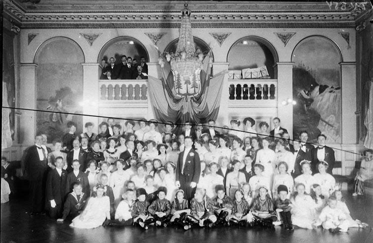 """Enligt tidigare noteringar: """"Gruppfoto från tillställning i festsalen på Grand Hotell."""""""