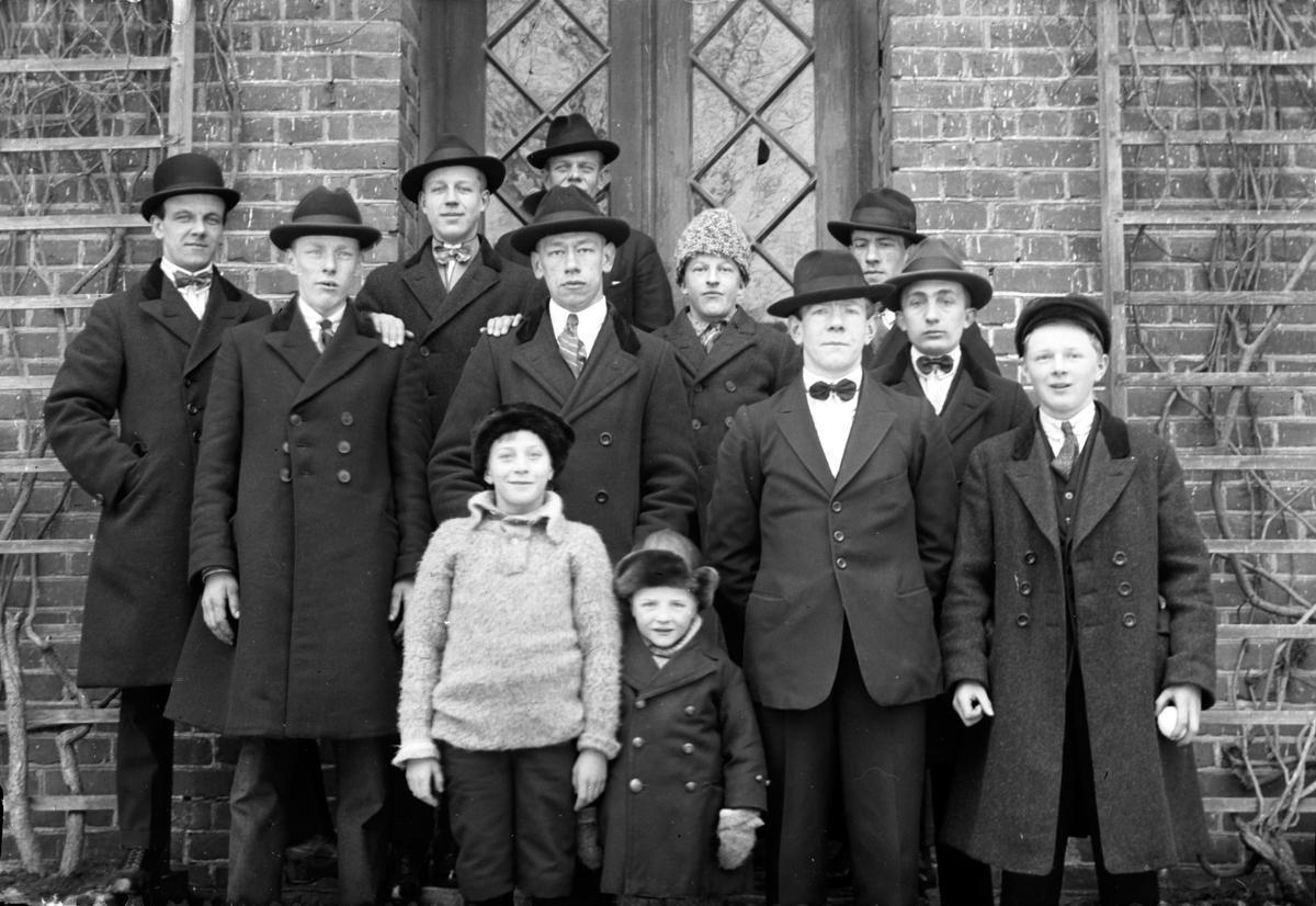 Åtta män samt två äldre och två yngre pojkar står framför ett tegelhus med glasdörrar i kvarter Jägmästaren, Jönköping.