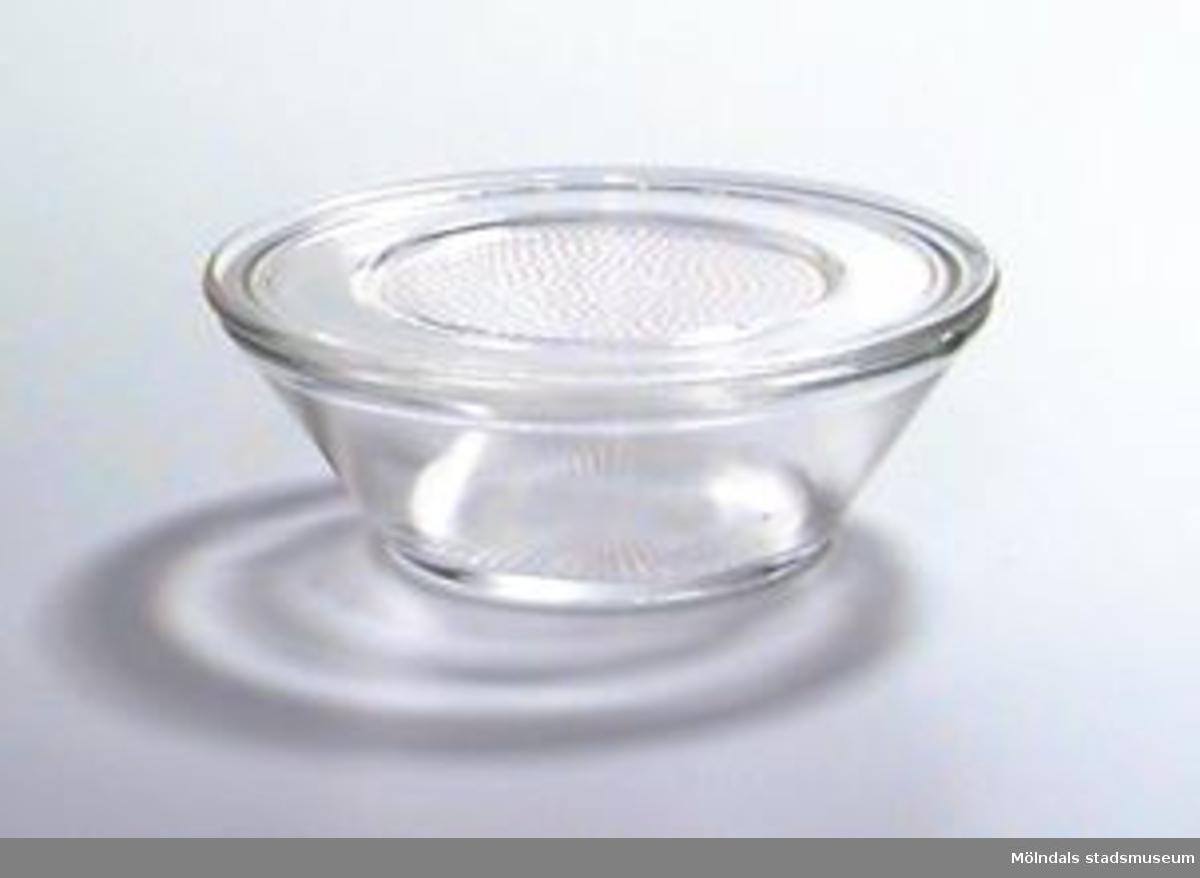 Rund glasskål, vidare upptill än i botten. Med lock. Räfflad i botten. Inom en cirkel på locket finns en mängd runda små upphöjningar.Ägaren är givarens mor.