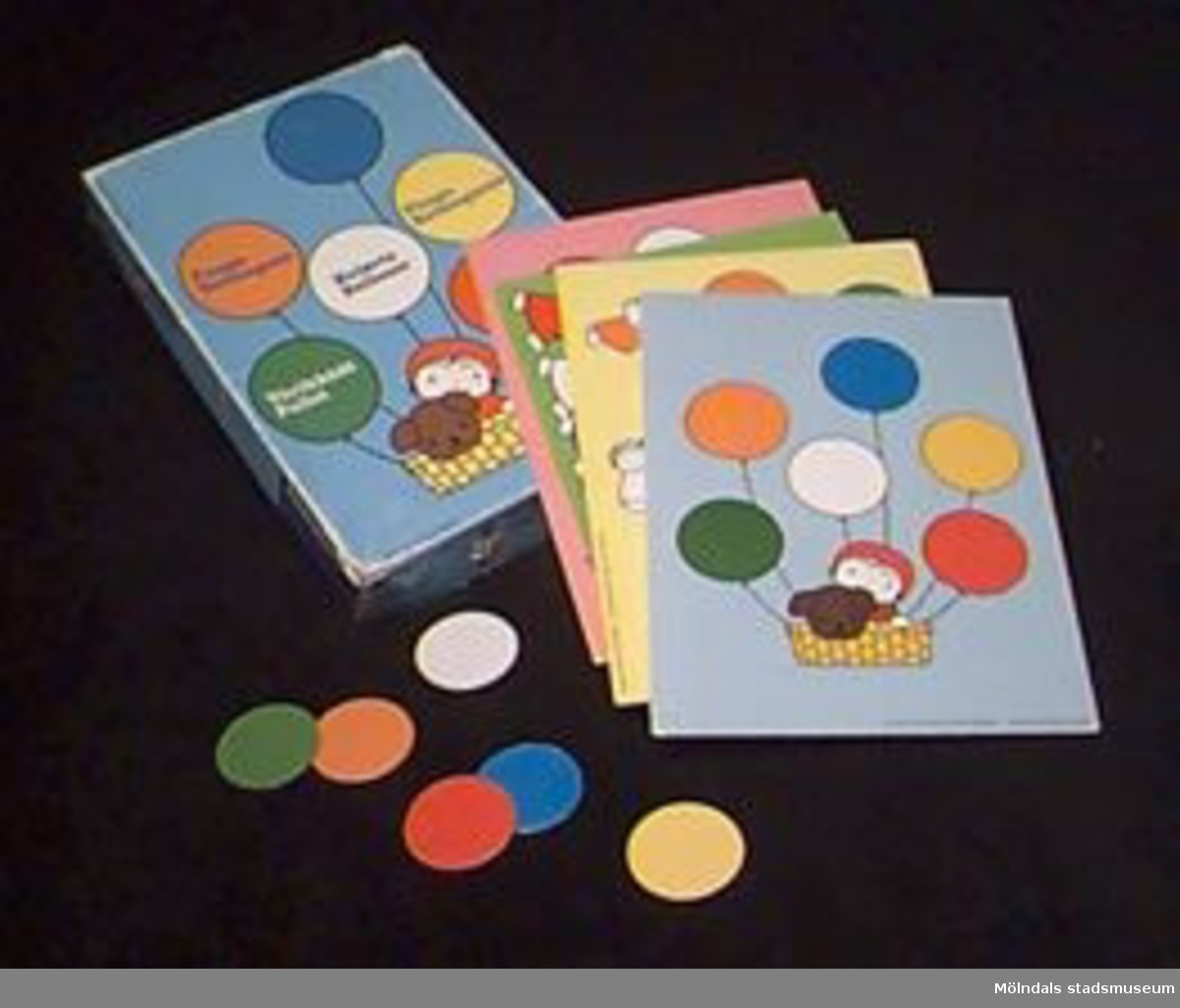 """Ask innehållande spel för barn 3-7 år. Spelets namn: """"Fånga ballongerna"""".Asken innehåller fyra spelbrickor (L: 270 mm. B: 190 mm.) i skilda färger med plats att placera ut sex ballonger på vardera bricka. Dessutom 24 ballonger (4 gula, 4 gröna, 4 vita, 4 blåa, 4 oranga och 4 röda) i form av runda pappbrickor (40 mm i diam).Spelregler och tärning saknas.Tidigare sakord: spel, leksaks-.Katrinebergs daghem var daghem."""