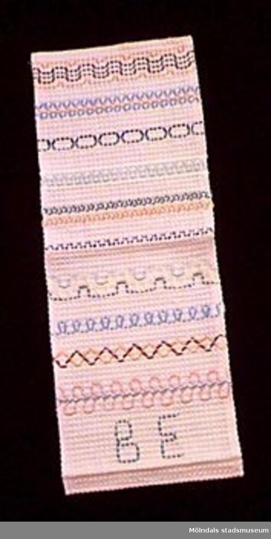 Ett stycke broderat rosa bomullstyg i våffelväv. Broderat i gröna, blå, rosa, gula och bruna färger. Olika dekorativa mönster utförda som provtekniker. Undervisningsmaterial för åk 3 och 4. Samhör med 02653-02661.Övriga uppgifter se 02643:1.