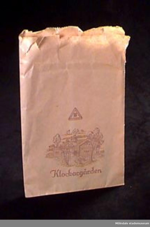 """En brun papperspåse med tryck i mörkbrunt: en teckning av ett hus med träd runt, texten """"Klockargården"""" samt en triangel med texten """"Klockargårdens hemslöjd"""". I triangelns mitt en vapensköld med en krona överst.  På huset står också """"hemslöjd"""".Gunvor Otter (f. 1916-12-21), ursprungligen från Gävle, flyttade till Toltorpsdalen (Fotbollsgatan 17) 1959. Till Bifrost flyttade hon 1991. Gunvor Otter är f.d. gymnasielärare i historia och svenska. 1955-1971 ca arbetade hon på Flickläroverket, därefter på Hvitfeldtska fram till pensioneringen 1981."""