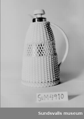 Termos (TV-kanna) tillverkad i metall med ljusgult plasthölje. Ett plastband är korgflätat runt kannan och handtaget. I botten finns märkningen 'AB TERMOVERKEN JÖNKÖPING' och på locket 'PAT.ANS. KOKHETT 1450-59'. Termosen är inköpt till utställningen 'Folkhemmets bostäder'.