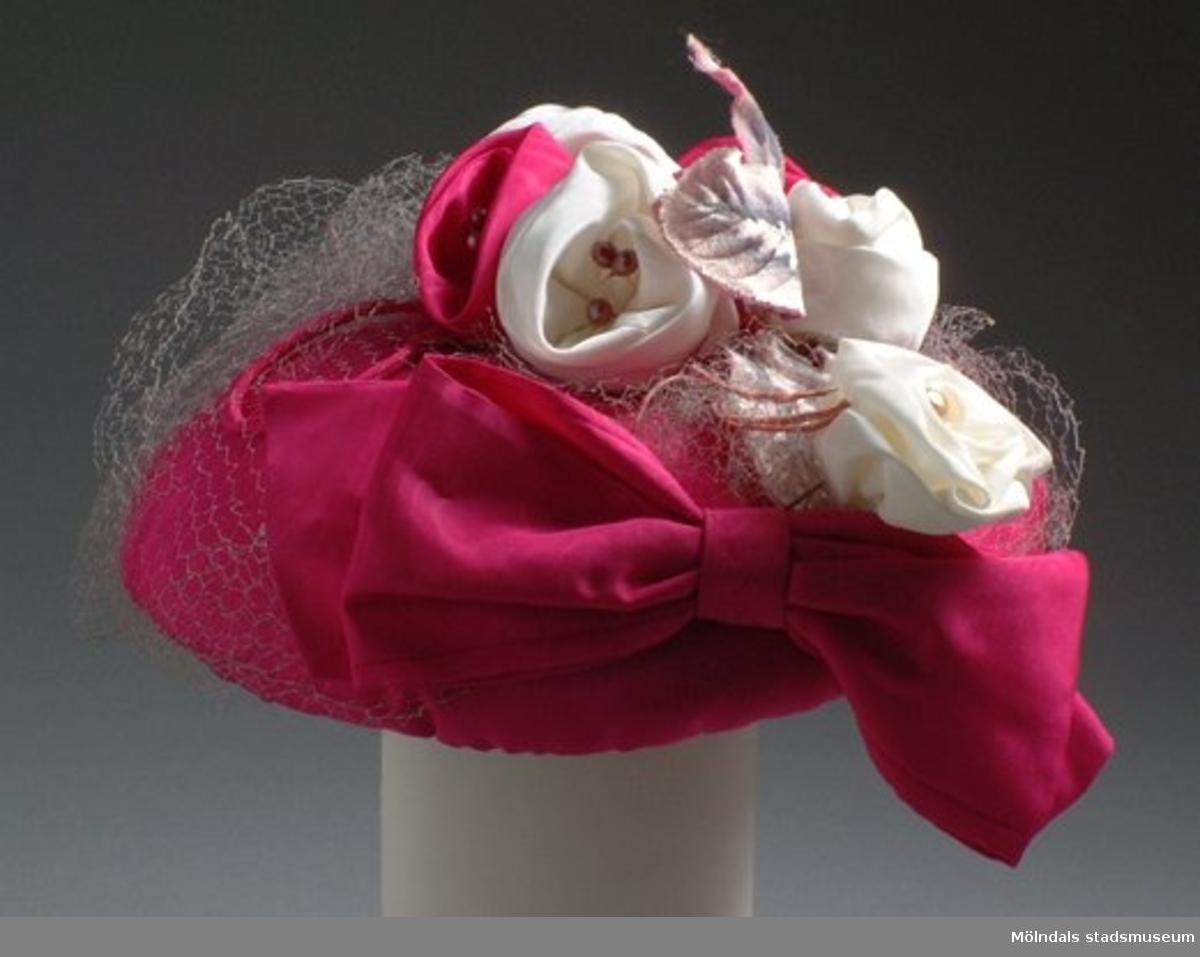 Ceris damhatt med flor, rosett, rosor, pärlor och blad. Rosorna är både i ceris och vitt. Hatten har likadana rosor fastsydda som tillhörande klänning med inv.nr: 03335_1-3. Det finns också tillhörande handväska invnr: 03336 och skor med inv.nr: 03337.Denna hatt låg i samma hattask, inv.nr: 03404, som hatt med inv.nr: 03338.