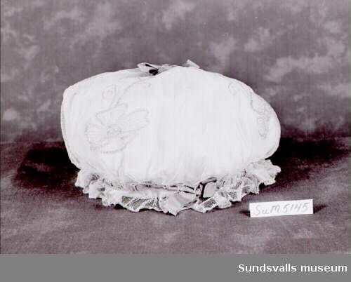 Nattmössa av vit tyll med lila broderade blommor och lila ripsband. Fodrad med vitt tyg. Enligt anteckning har nattmössan använts av 'A:s farmor'.