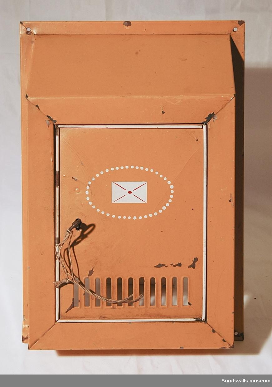 Brevlåda i gulmålad plåt med låsförsedd öppningslucka. Luckan är nertill perforerad och är också dekorerad med ett målat kuvert omgivet av prickar. Brevlådan skruvas fast på en vägg eller liknande. Ett hål i varje hörn. Nyckel.