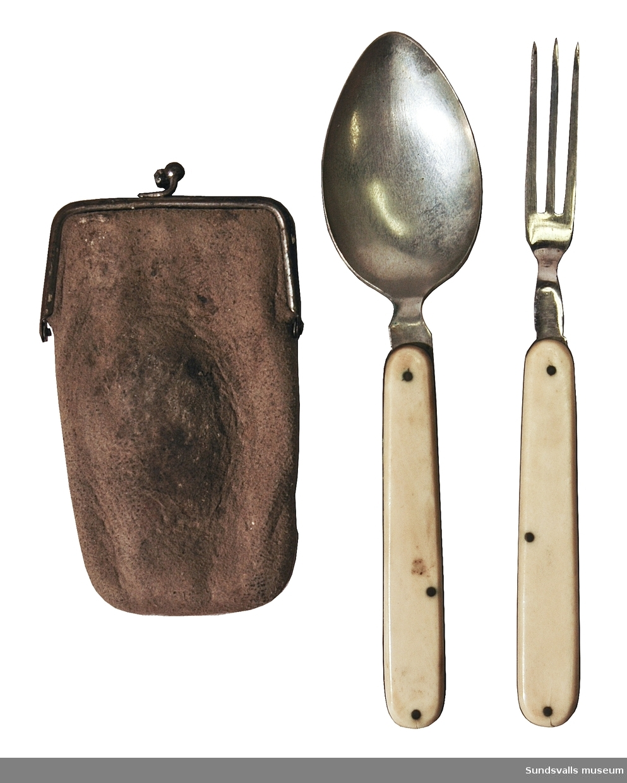SuM 5677:1-6 resebestickset bestående av sked och gaffel i fodral, samt två borstar i fodral. Besticken förvaras hopfällda. Skaft av ben. Längd 16,5 cm utfällda. Fodralen är tillverkad i sämskskinn. Två borstar i liknande fodral.  Borstarna är 9 cm långa.