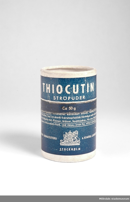 Medicinburk av rund pappkartong med lock. Innehåller Thiocutin Ströpuder som används för hudproblem. Liten rund etikett från apoteket i Mölndal på locket.