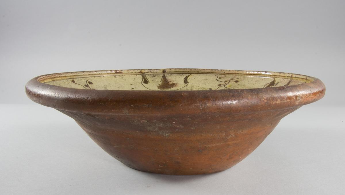 Fat i keramik, djupt. Ljust gul till färgen med blomsterdekor i gult och brunt. På spegeln även årtalet 1796. Undersidan omålad. Missfärgad, gröna fläckar.
