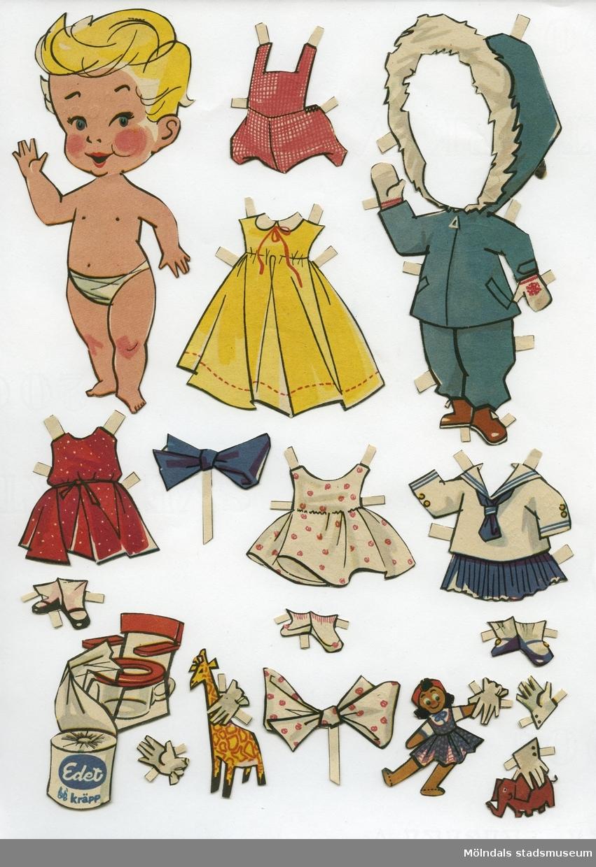 """Klippdocka med kläder och tillbehör från 1950-talet. Docka och kläder är märkta med """"Diana"""" på baksidan - dockans namn. Dockan är urklippt ur tidning, och är också reklam för toalettpappret Edet Kräpp. Dockan föreställer ett litet barn, tecknat, med blont hår, iklädd blöja/underbyxa.Garderoben består av uteplagg (jacka med kapuschong och byxor), två kortare klänningar, en längre klänning, sjömanskostym med kjol, lekdräkt med korta ben, två scarves, tre par skor med strumpor, leksaker, samt en potta med tillhörande rulle Edet Kräpp.Docka och kläder förvaras i kuvert, 12,5x15,5 cm. Tryckt avsändare är Nordiska Beklädnadskompaniet, Ulricehamn. Kuvertet är märkt """"Diana"""" och """"Laila"""" (MM04576), samt ett urklippt rim: """"Jag är från Lilla Edet Hoppas att du ser det! Och här är mina, fina kläderför vinterbruk och sommarväder.  Klipp nu ut och klä mej så ska jag leka med dej."""""""