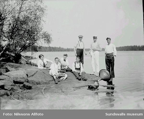 Människor sitter vid sjön och spelar på en vevgramofon.