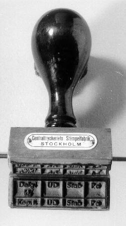 Stämpel med skaft av trä och stämpelyta av gummi. Stämpelnger avtrycket:se MRK. På stämpelns ena sida finns en litenmetalllatta med texten:Centraltryckeriets Stämpelfabrik STOCKHOLM.