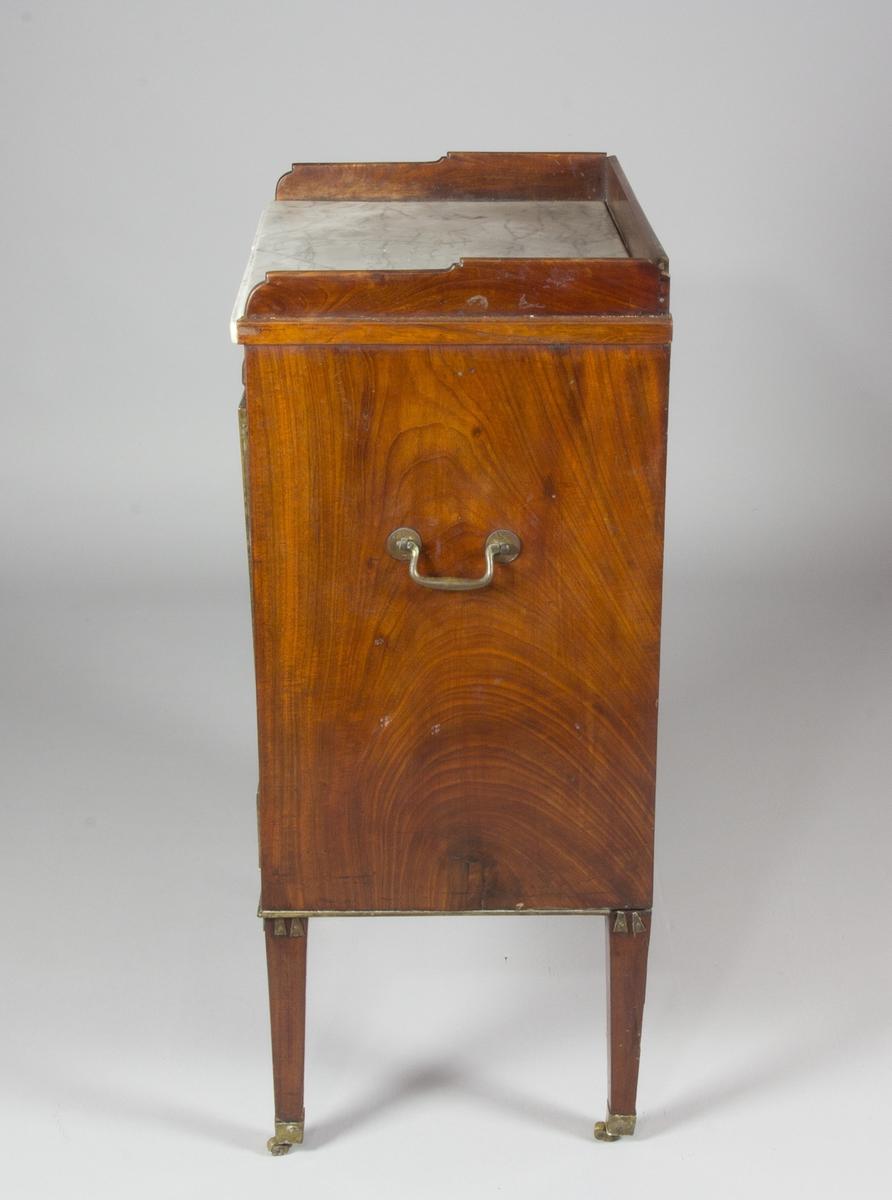 Kommod av mahogny. Med trågformade mahognylistor och skiva av marmor. Nedanför skivan en skiva av trä att dra ut. Med klaffdörr och  låda med lister, beslag och knopp av mässing. Fyra avsmalande ben på trissor av mässing. Benen upptill dekorerade med mässingsbeslag. Sidorna med bärhandtag av mässing.