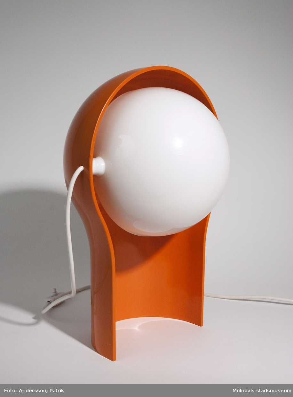 """Bordslampan Telegono från IKEA. Formgiven av den italienska arkitekten och möbelformgivaren Vico Magistretti för IKEA på 1970-talet.Bordslampan är av orange hårdplast och har en reglerbar lampkupa av vit porslin. Strömsladden är vit. På strömbrytaren står det gjutet i plasten: """"2A   250V"""" och """"3030"""".MåttBredd: ca. 255 mm, Höjd: ca. 390 mmLängd på sladd: 1790 mm"""