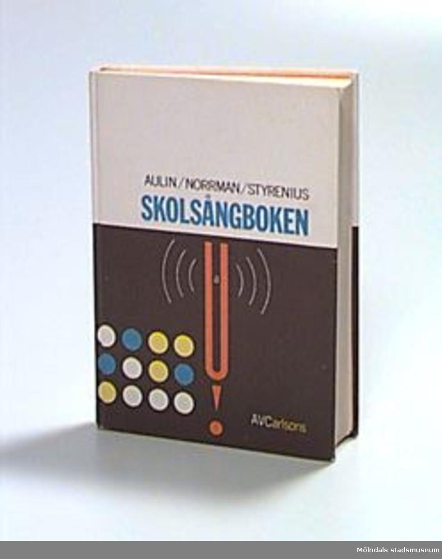 """Omslag i svart och vitt med abstrakt illustration i gult, blått och rött. Text i svart, blått, vitt och gult. Titel: """"Skolsångboken"""". Författare: Aulin/Norrman/Styrenius. Stämpel på sidan tre: """"Mölndals museum"""", samt skrivet med blyerts: """"Xqh"""", ämneskod från museets bibliotek, där boken tidigare var placerad.Skrivet med blyerts på näst sista bladet: """"G. Anna-Lisa Johansson. Hennes son Ingemar Tidefors har haft den i skolan. 17/10 -90""""."""