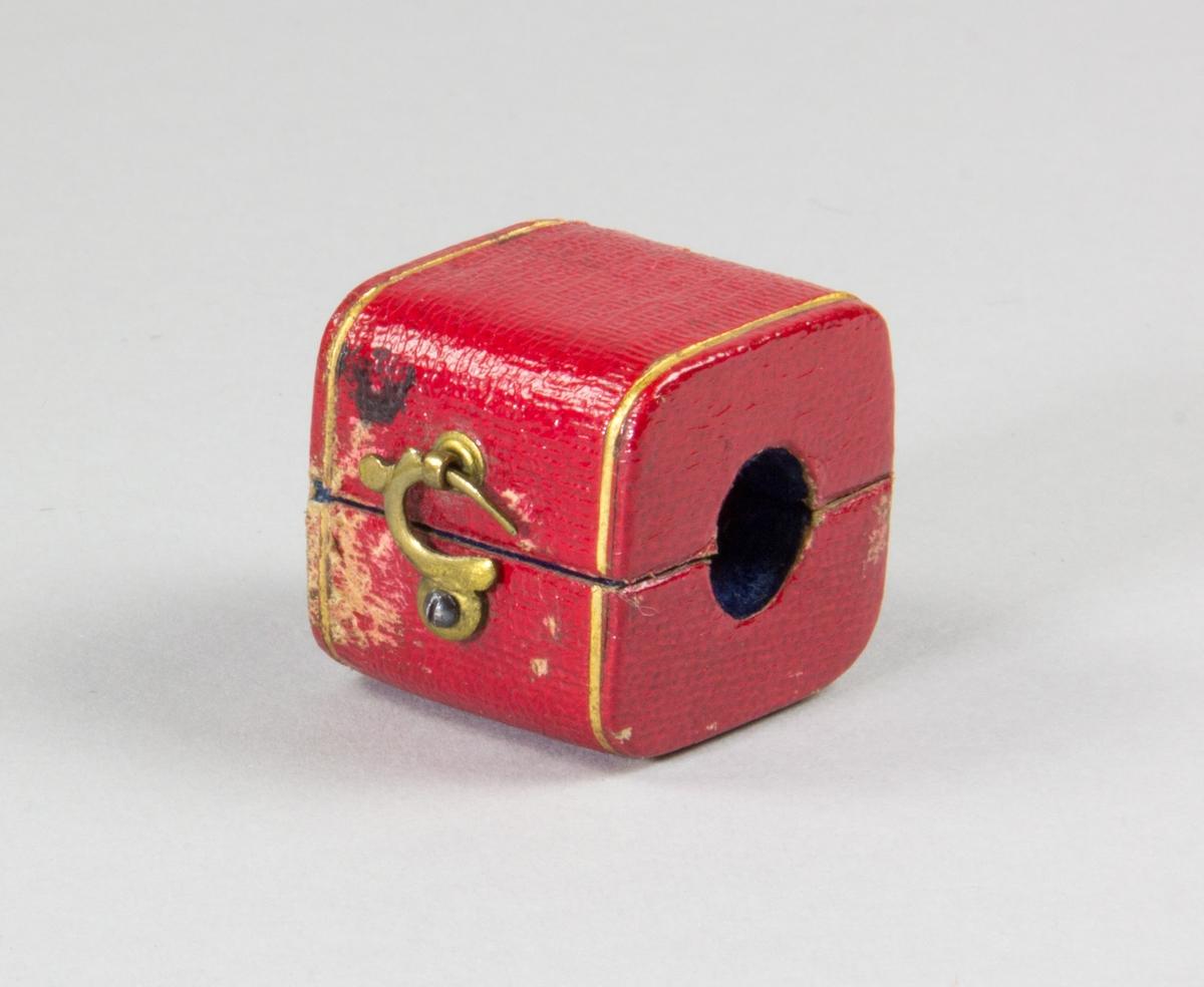 Etui av papp klädd utvändingt med rött läder, samt invändigt med blått sammet. Etuiet invändigt utformat för att omsluta ett sigills stämpelplatta. Ena kortsidan av etuiet med hål för sigillstampens skaft. Etuiet stängs med en liten böjd hasp av metall.