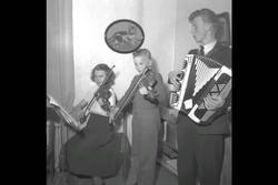 Musik hos Melander i Bydalen. Kvinnor i dräkter dukar upp tå
