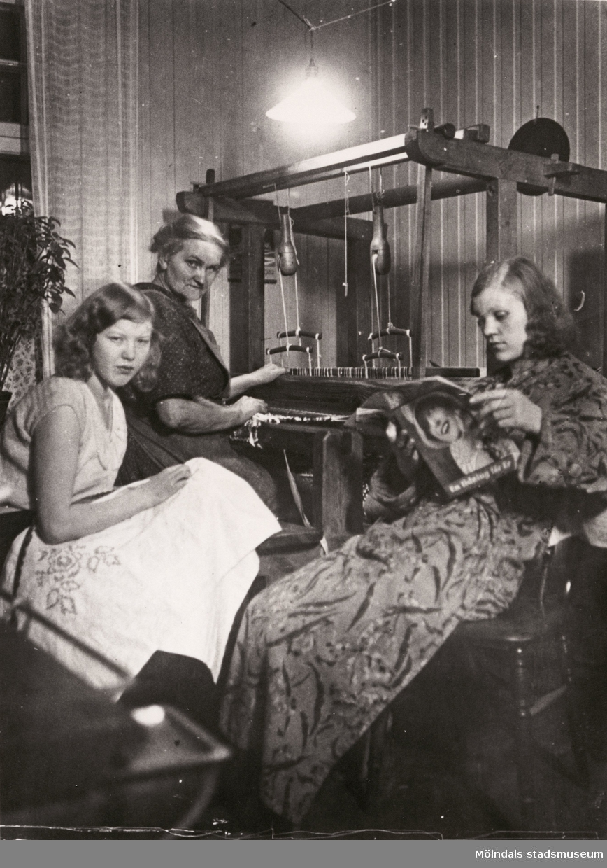"""Kvinnorna i familjen Hansson väver, syr och läser i köket år 1932. """"På detta foto sitter farmor och väver. Det är inget låtsas för hon vävde många trasmattor som hon drog ihop pengar till familjens uppehälle på. Dessutom var hon sömmerska. Allt detta gjorde hon i hemmet. Farfar arbetade på Papyrus i alla år. Hans äkta tunga guldmedalj som han fick """"efter lång och trogen tjänst"""" har jag fått ärva. Mamma då 19 år tittar mot kameran och Brita läser tidning."""" (berättat av Hans Hansson)"""