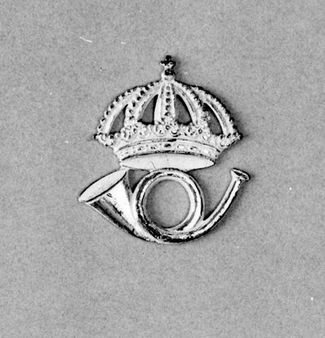 Mössmärke i vitmetall av den modell som fastställdes 1912.