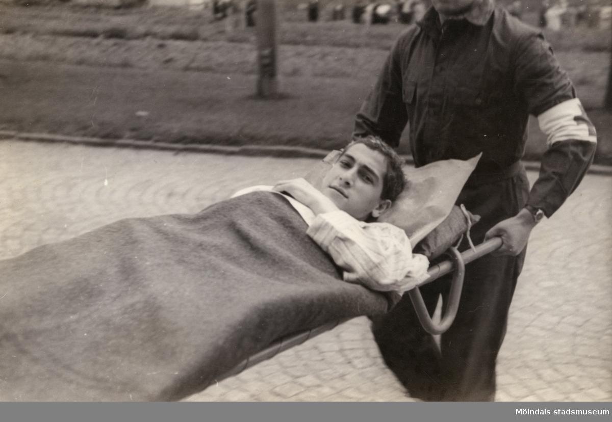 """""""Karantänsförläggning"""" på Kvarnbyskolan för flyktingar från koncentrationsläger i Tyskland 1945. En manlig flykting på bår buren av en Röda Kors-personal."""