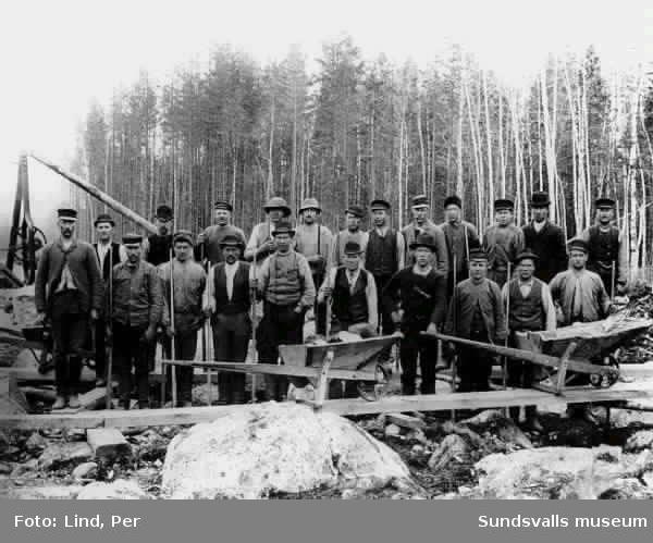 """Alby 1898.""""Grupp vid turbingropen"""". Gruppbild med arbetare utrustade med spett. I bildens framkant två skottkärror."""
