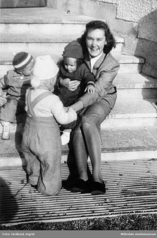Fröken och några barn sittandes på en trappa vid ett daghem i Guldheden, Göteborg, 1940-tal.