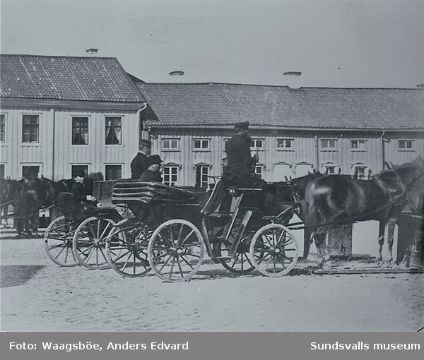 """Droskor med kuskar och passagerare på Stora torget. Rådhuset efter branden 1803, till vänster det så kallade """"Forsstedska huset""""  var rådhus till 1867 då det nuvarande togs i bruk."""