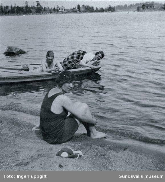 Badliv vid Spikarna. Juno Wikner på stranden. Flickona i båten (till vänster Anny Näslund) var uppasserskor på stadshusrestaurangen. Att hyra stuga på Alnön över sommaren tillsammans med 6-8 kamrater var vanligt.