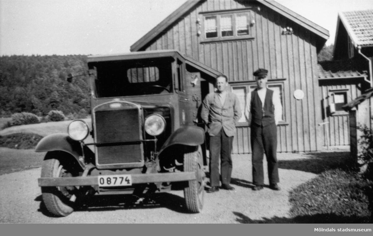 På 1920-talet bytte Anderstorps fabriker ut hästtransporterna  mot biltransport. Här står chaufför Robert Börjesson vid den första bilen. Bredvid står lasthjälpare Erik Göransson.