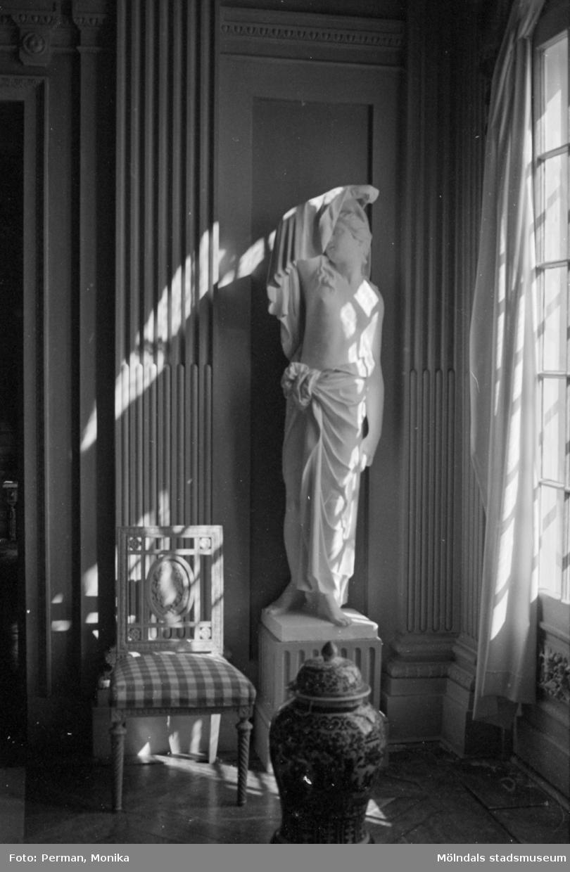 Dokumentationsfoto från Gunnebo slott våren 1992. Inredningsmiljö, konstföremål och möbler av varierande slag. Här ses en stol, en skulptur på en piedestal samt en vas vid en vägg.