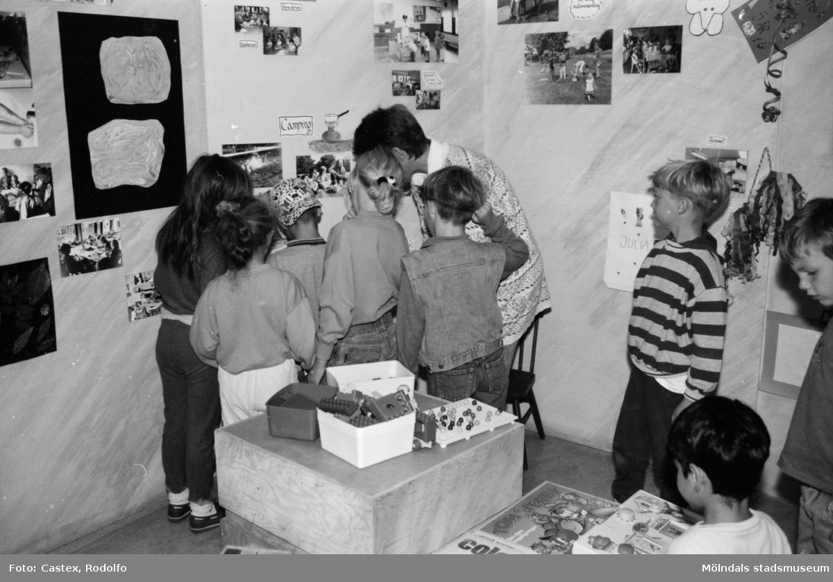 Några barn och en vuxen tittar på foton som sitter uppsatta på en vägg. Utställningsvernissage av och om Katrinebergs daghem på Mölndals museum 1993-09-10.