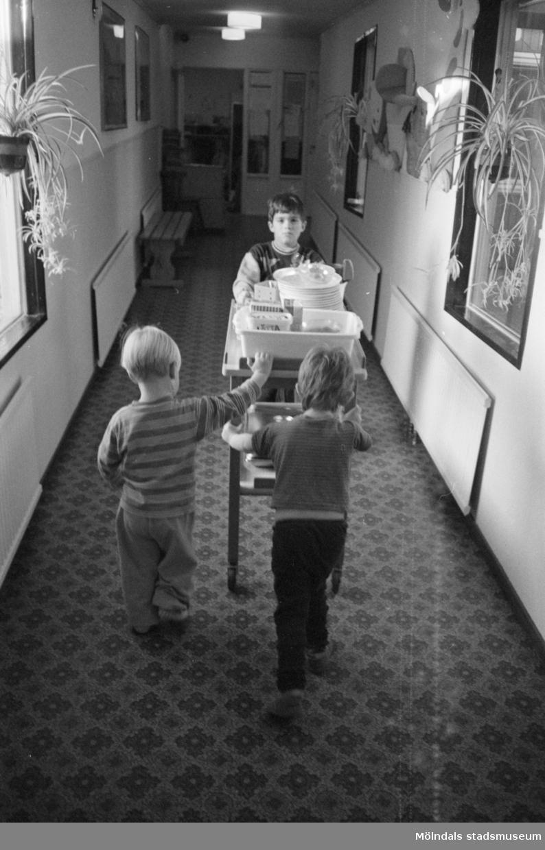 Robin, Fred och Alexandra går med en matvagn i korridoren vid Lunkentussen, Katrinebergs daghem, 1992-93.