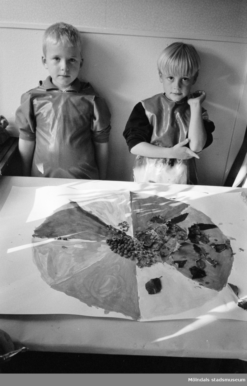 Två pojkar, iklädda förkläde, står uppställda bakom ett bord där det ligger en stor målad teckning, dekorerad med bl.a blad. Båda gossarna tittar mot kameran. Katrinebergs daghem, 1992-93.